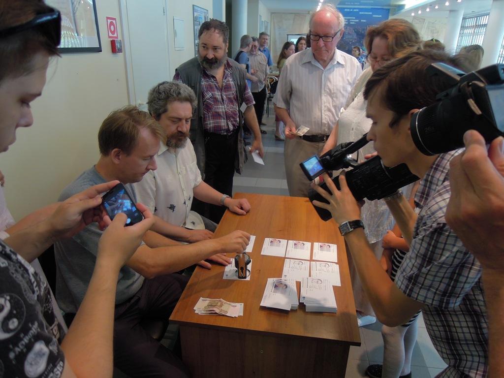 Гашение карточек специальным юбилейным штемпелем с портретом И. Лаврова